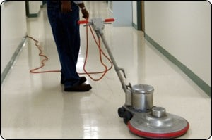 facilities maintenance employee cleaning a hallway